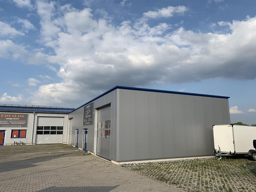 Betriebserweiterung: Pultdachhalle mit Attika, Dach aus Isopaneel, Kastenrinne mit Innenentwässerung.